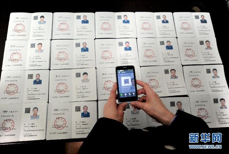 局,一名民警用手机扫描带有二维码的新版《保安员证》.&#